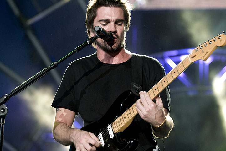 Juanes playing the guitar in a concert