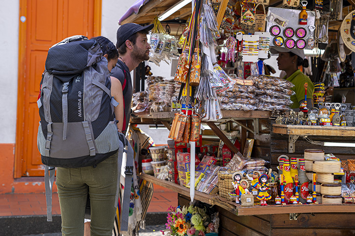 Guy buying handicrafts in Medellin and girl with a backpack